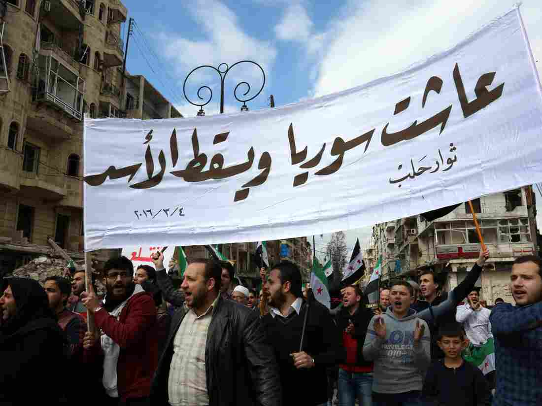"As the cease-fire took hold this week, Syrians lost no time returning to the streets to protest the Assad regime. Marchers hold a banner reading ""Long live Syria, down with Assad"" during an demonstration in the rebel-controlled side of Aleppo on Friday."