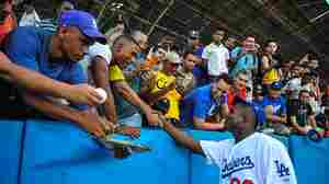 Los Angeles Dodgers star Yasiel Puig shakes hands with fans Dec. 16 at the Latin American Stadium in Havana during a Major League Baseball goodwill tour. Puig and fellow Cuban national Jose Abreu of the Chicago White Sox returned home Tuesday for the first time since defecting — Puig in 2012, Abreu in 2013 — to join the American big leagues.