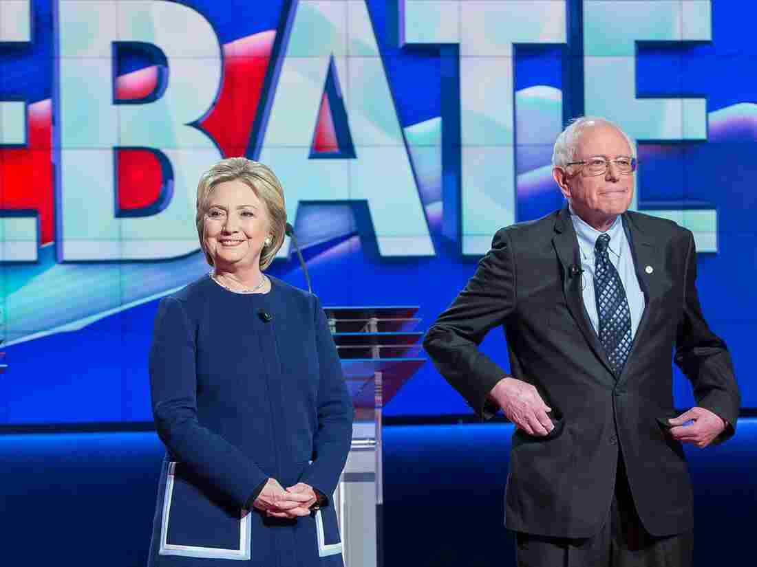 Hillary Clinton and Bernie Sanders await the start of the Democratic presidential debate in Flint, Mich., on Sunday.