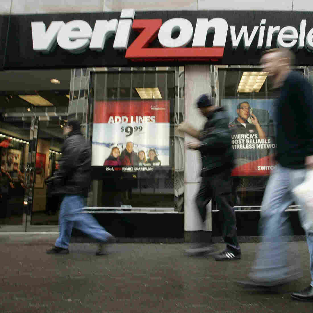 Pedestrians walk past a Verizon Wireless shop.