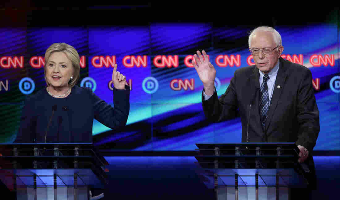 Democratic presidential candidate Hillary Clinton argues a point as Sen. Bernie Sanders reacts during Sunday's Democratic presidential primary debate at the University of Michigan, Flint.