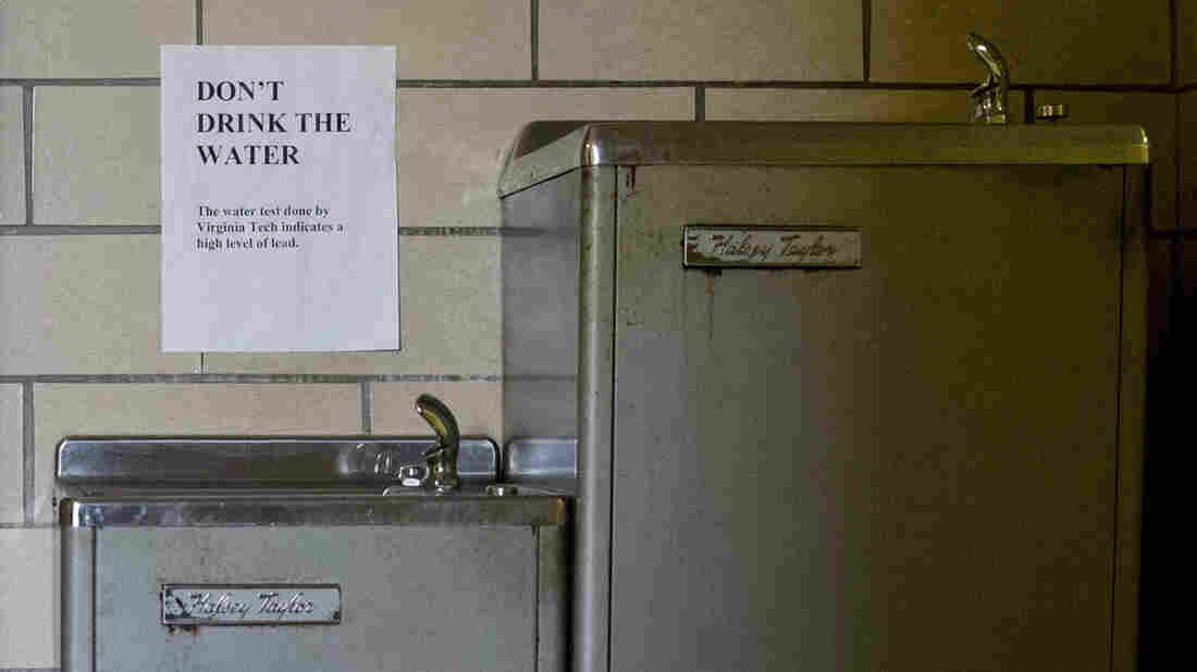 Seven families are part of a new federal lawsuit that seeks class-action status in Flint, Mich. Here, signs warn not to drink lead-contaminated water from a water fountain at a church in the city earlier this year.