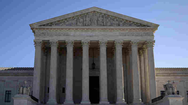 Visitors walk outside the U.S. Supreme Court on Feb. 14. The court announced on Monday that it has unanimously reversed an Alabama Supreme Court ruling that denied parental rights to a lesbian adoptive mother who had split with her partner.