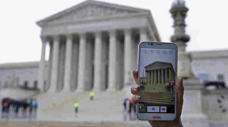 A visitor takes photos with her smartphone outside the Supreme Court in 2014, while the judges heard arguments related to warrantless cellphone searches by police.