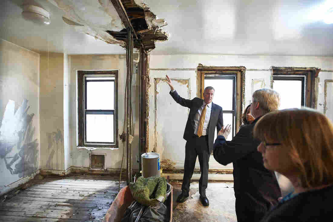 New York City Mayor Bill de Blasio (left) tours an apartment under renovation in the Bronx borough of New York last April. The building is one of four buildings that will lock in a 30-year affordable rental agreement.