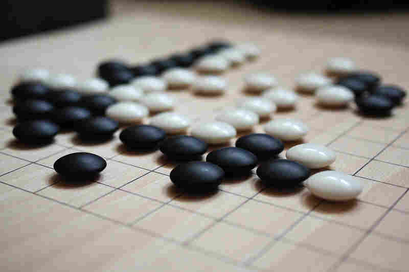 In the game of Go, players try to seize territory and encircle each other's pieces.