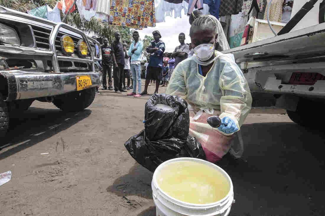 Garmai Sumo mixes chlorine with water to disinfect a residential area in Monrovia, Liberia, where a resident died of Ebola on Oct. 14, 2014.