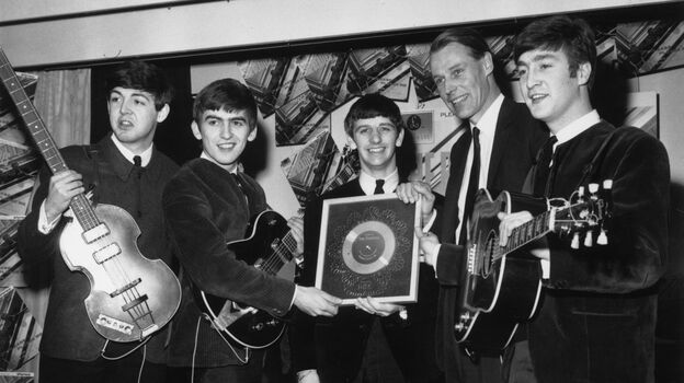 The Beatles in 1963 with their first silver record. (From left) Paul McCartney, George Harrison, Ringo Starr, producer George Martin and John Lennon. (Getty Images)