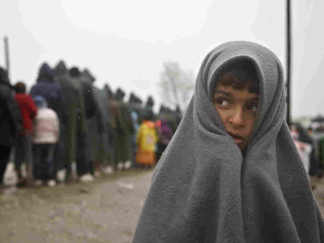 A migrant child covered by a blanket stands in the rain at the northern Greek border station at Idomeni on Thursday.