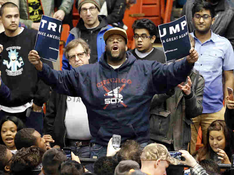 A protester holds up a ripped campaign sign for Republican presidential candidate Donald Trump before a rally on the campus of the University of Illinois-Chicago on Friday. The rally was canceled amid security concerns.