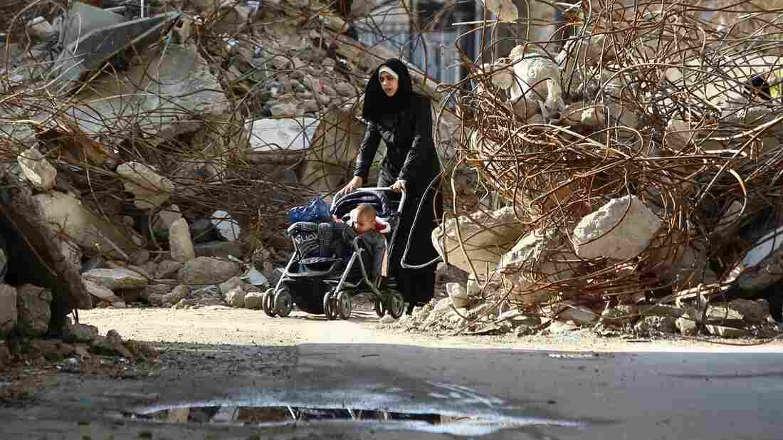 A woman navigates a stroller between the rubble of destroyed buildings in the rebel bastion of Douma, Syria, in December 2014. A new report card on the international response to Syria's violence faults the U.N. Security Council.