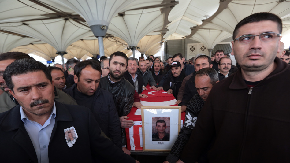 Family members and friends carry the Turkish flag-draped coffin of Murat Gul, 20, a security agent killed in Sunday's explosion, during his funeral procession in Ankara, Turkey. (Burhan Ozbilici/AP)