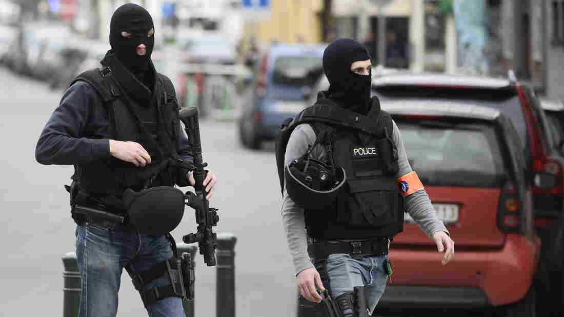 Police officers walk in the area of a shooting in the southern Forest district of Brussels on Tuesday. Shots were fired at police as they carried out an operation prosecutors say was linked to the Paris attacks of last November.