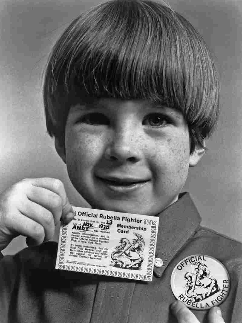 """A little boy shows off the """"Official Rubella Fighter"""" membership card and button he received after being immunized against the German measles. This public health campaign against the virus ran through the early 1970s."""