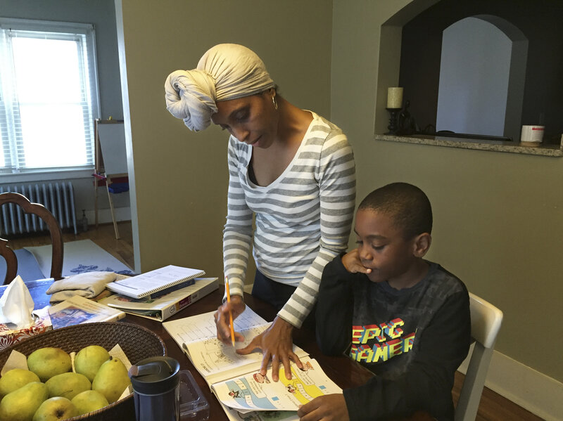Camille Kirksey helps Brandon with math at the dining room table. Kirksey says black children at Brandon's private pre-K weren't given the kindness she thought they needed, so she decided to home-school him.