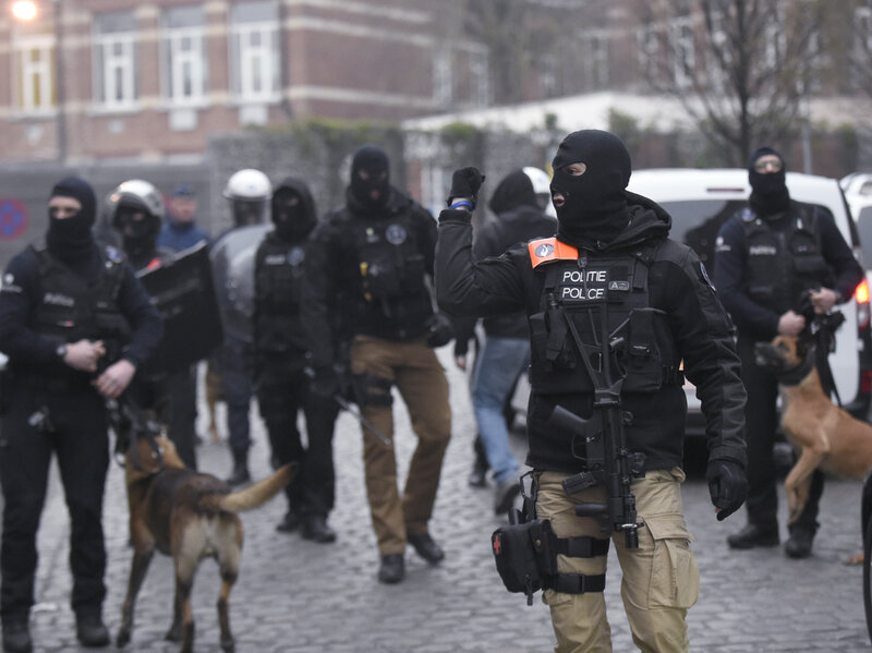Belgian policemen walk in a street during a police action in the Molenbeek neighborhood in Brussels on Friday.