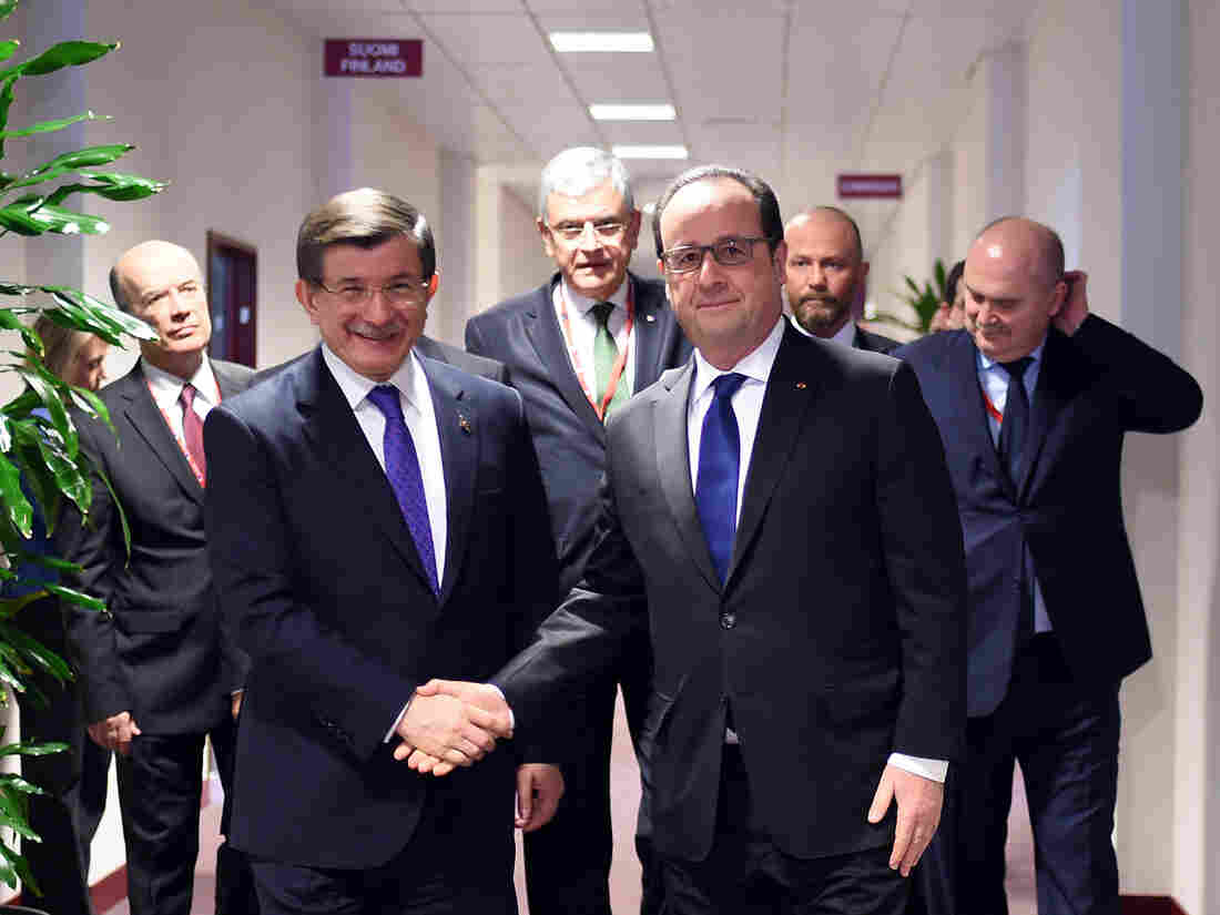 French President Francois Hollande (center right) shakes hands with Turkish Prime Minister Ahmet Davutoglu, (center left) before a meeting during an EU summit in Brussels on Friday.