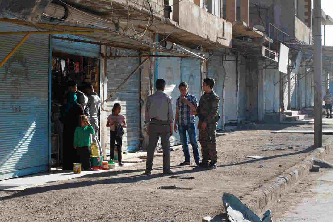 Residents talk to a Kurdish fighter in Shadadi, recently retaken from ISIS. The U.S.-backed Syrian Democratic Forces which have moved into the city are dominated by an ethnic Kurdish faction. The town's residents are Arabs.