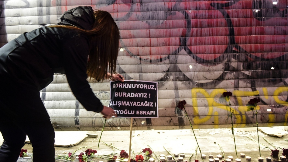 """A woman puts a placard at the site of a blast on Istiklal Street, a major shopping and tourist district, in central Istanbul, on Saturday. The sign reads in Turkish, """"We are not afraid, we are here, we won't adjust,"""" according to an AFP translation. (Bulent Kilic/AFP/Getty Images)"""