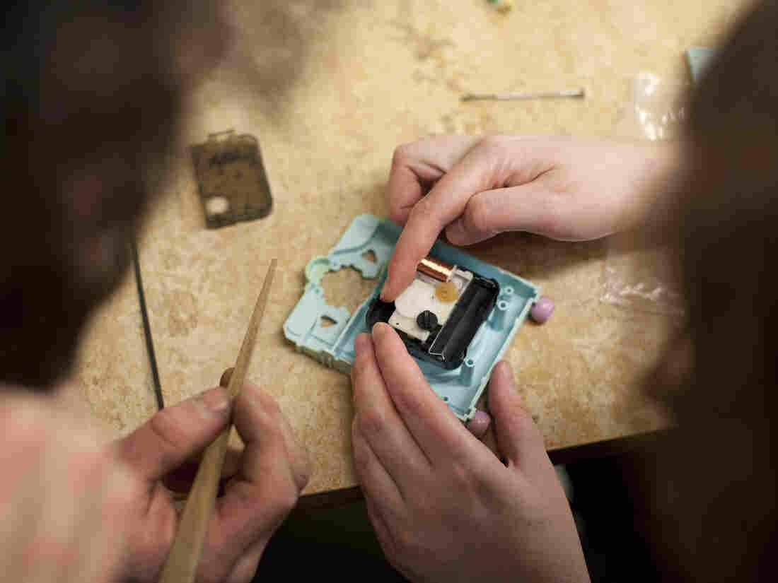 Esti Brennan (right) takes apart her Polly Pocket clock with the help of Matt McEntee.