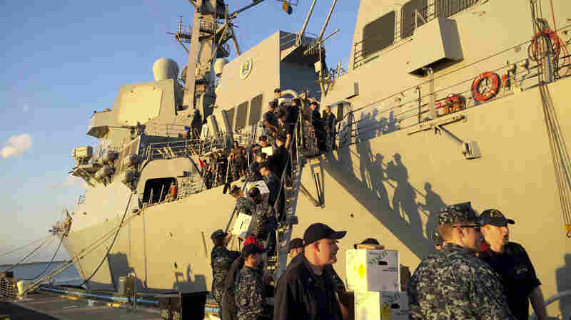 Crew members of the U.S. Navy destroyer USS Jason Dunham load supplies while docked in Guantanamo Bay, Cuba, in 2015. The U.S. and Cuba have restored diplomatic relations, but the U.S. says it remains committed to keeping the base.