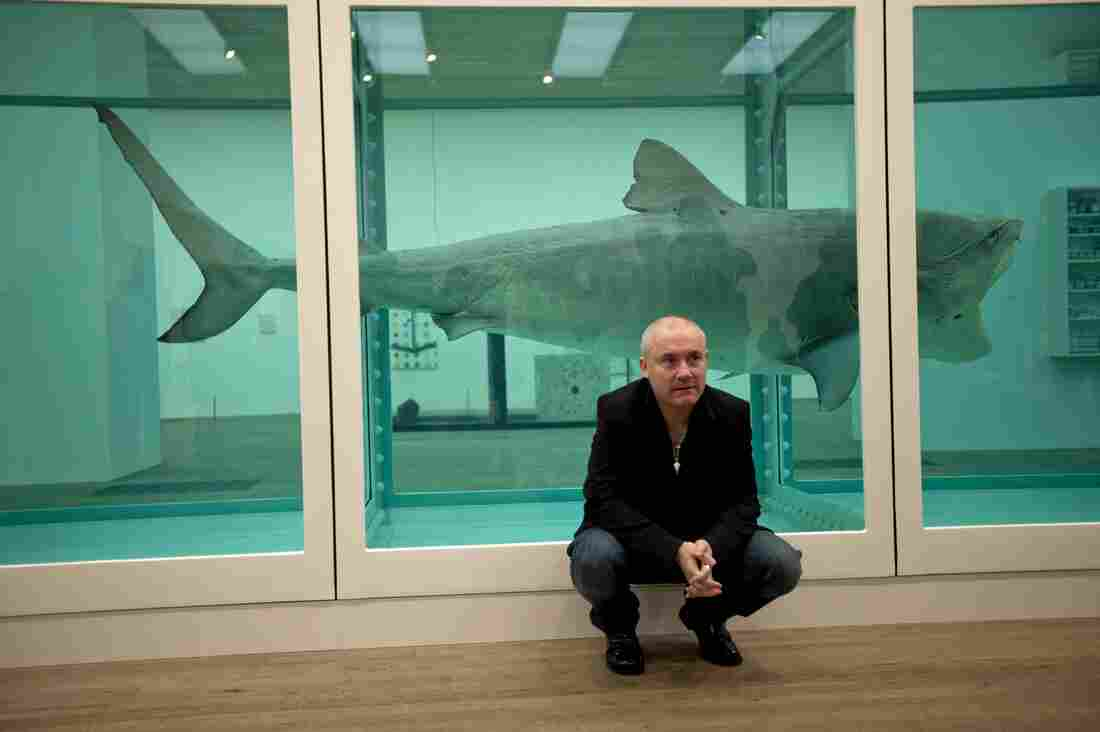 "British artist Damien Hirst beside the 1991 piece ""The Physical Impossibility of Death in the Mind of Someone Living,"" a tiger shark preserved in formaldehyde in a vitrine, in the UK at the Tate Modern gallery in London."