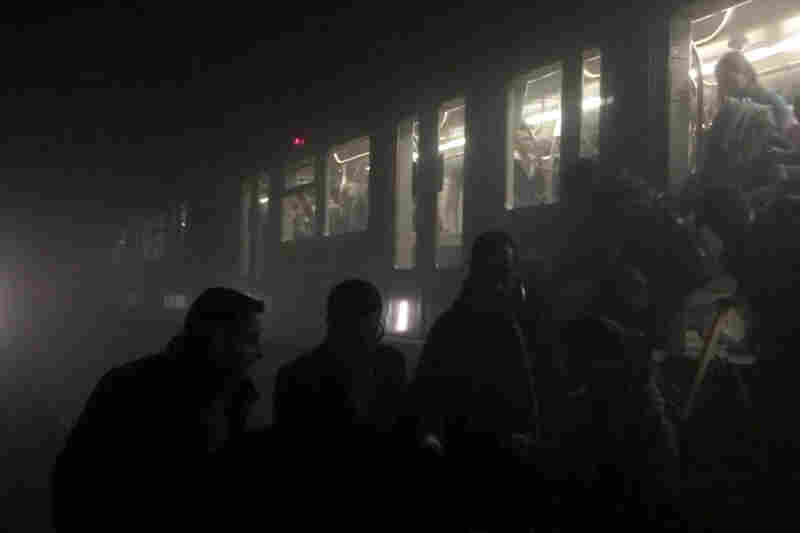 In this photo provided by Evan Lamos, passengers clamber from a metro carriage after the explosions in Brussels.