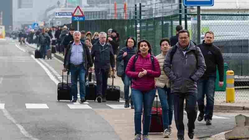 People walk away from Brussels airport after Tuesday's terrorist attack. Analysts say the violence may reduce travel for a while but the industry should bounce back.