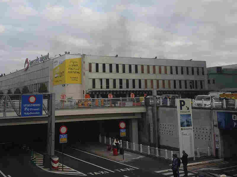 Smoke is seen at the airport in Brussels, Belgium, after explosions were heard Tuesday. Police are reporting at least one person was killed and the terror level has been shifted to maximum level.