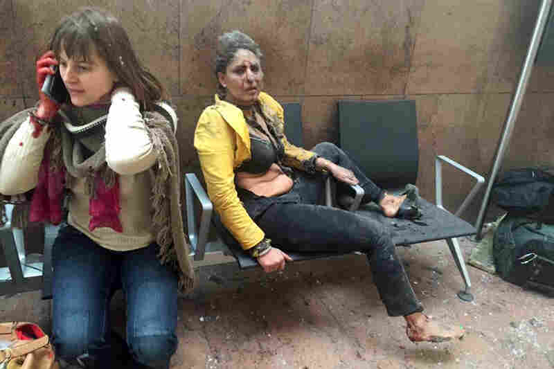 Two women sit in the airport in Brussels after the Tuesday morning explosions. The blasts hit near the departure gates, collapsing ceiling panels and shattering glass windows; Belgian media said 11 people were killed.