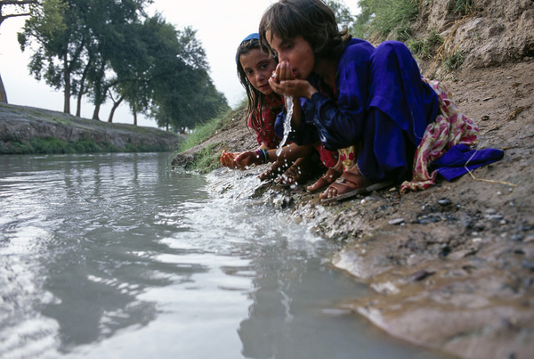 Young girls drink water from a canal flowing between nearby refugee camps and the main road in Peshawar, Pakistan.