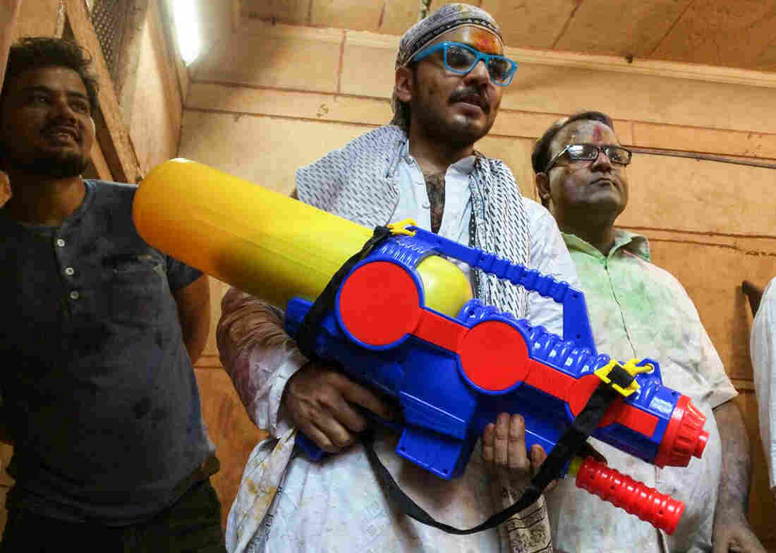 A devotee holds a water gun loaded with colored water during the Holi festival in Mathura, India.