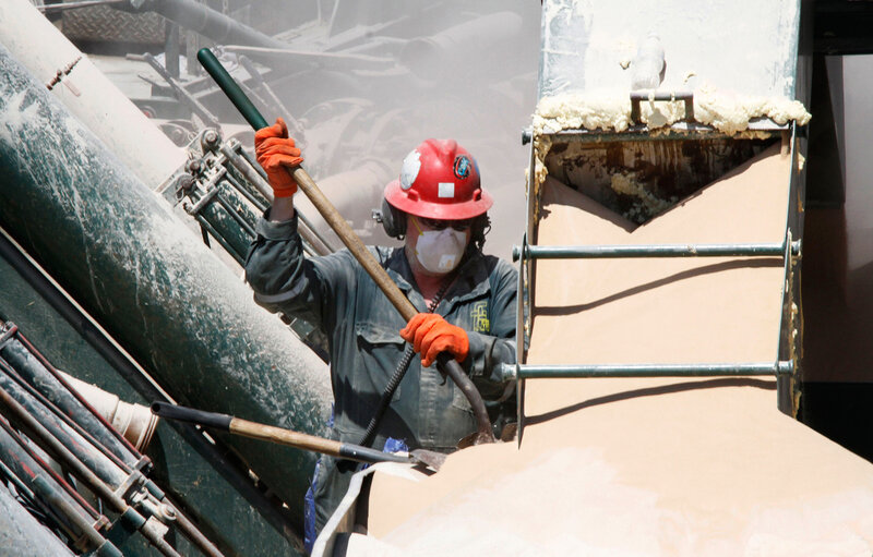 A worker in Claysville, Pa., shovels the fine powder that's part of a watery mixture used in hydraulic fracturing. Silica dust is created in a wide variety of construction and manufacturing industries, too.
