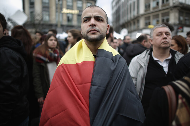 A man wears the Belgian flag as people observe a one minute silence Wednesday at the Place De La Bourse, in honor of the victims of Tuesday's terror attacks in Brussels.