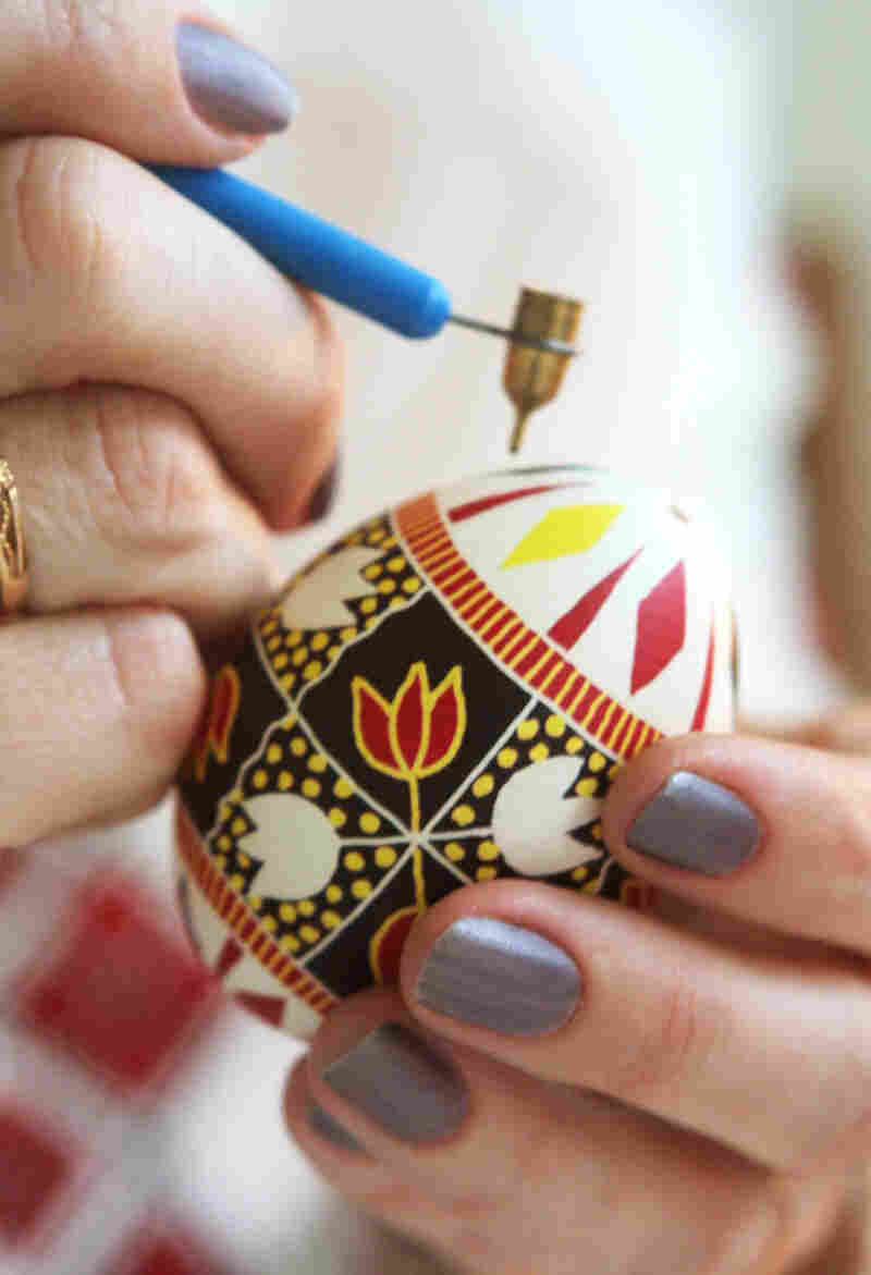 "Famous Ukrainian Easter egg artist Galina Ivanets paints her creation with a writing pin in her workshop in Kiev, Ukraine. ""Pysankarstvo"" — the art of painting Easter eggs — has enjoyed a renaissance as part of the religious and cultural awakening in post-Soviet Ukraine following decades of state-sponsored atheism."