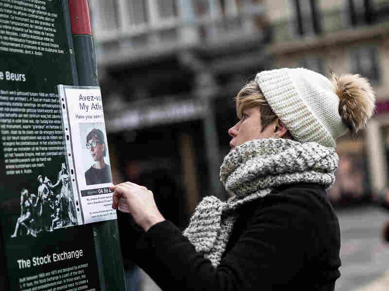 A woman looks at a poster of a missing person at a memorial for victims of attacks in Brussels on Wednesday.