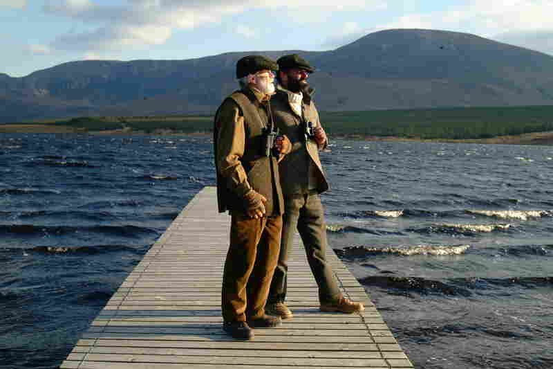 Tristan Donaghy and his father Kevin Donaghy, co-owners of Studio Donegal, wearing some of their hand-loomed tweed as they stand before the Slieve League mountain in northwest Ireland.