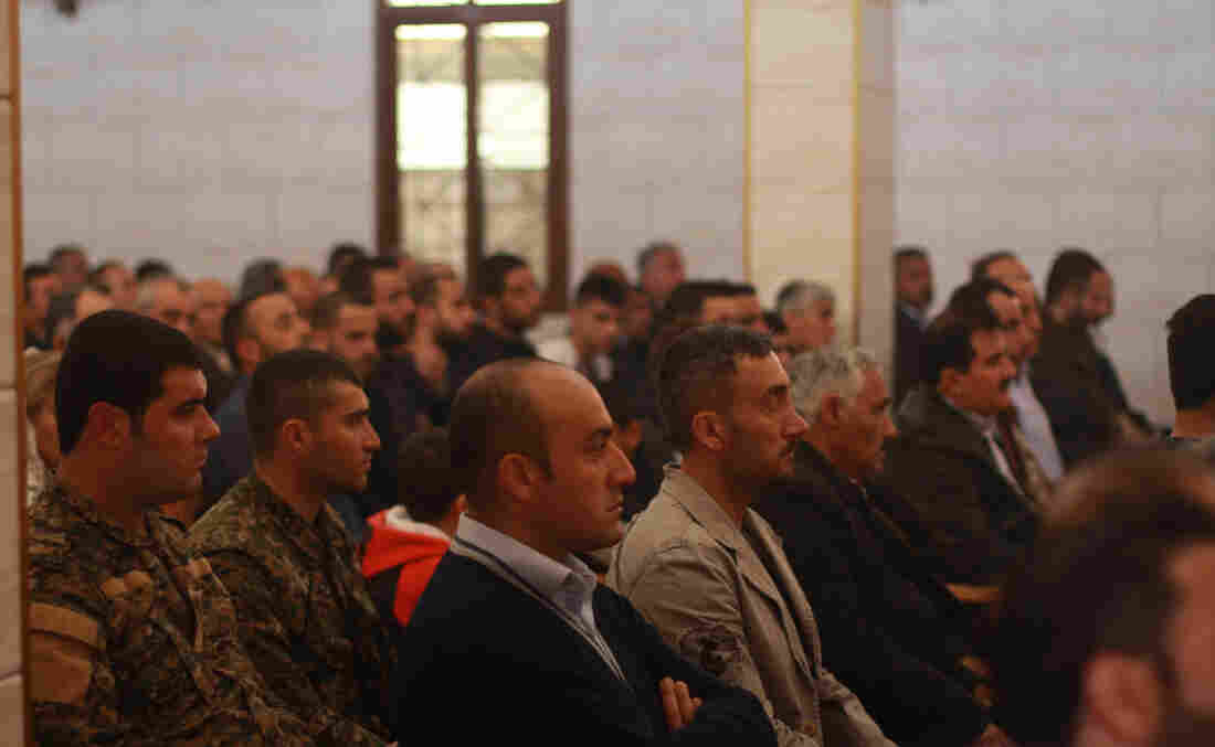 Front rows of the Church of Our Lady in Tell Tamer, Syria, are filled with Assyrian Christians. In uniform, left, is Kino Gabriel, spokesman of an armed Assyrian militia formed to protect from ISIS.