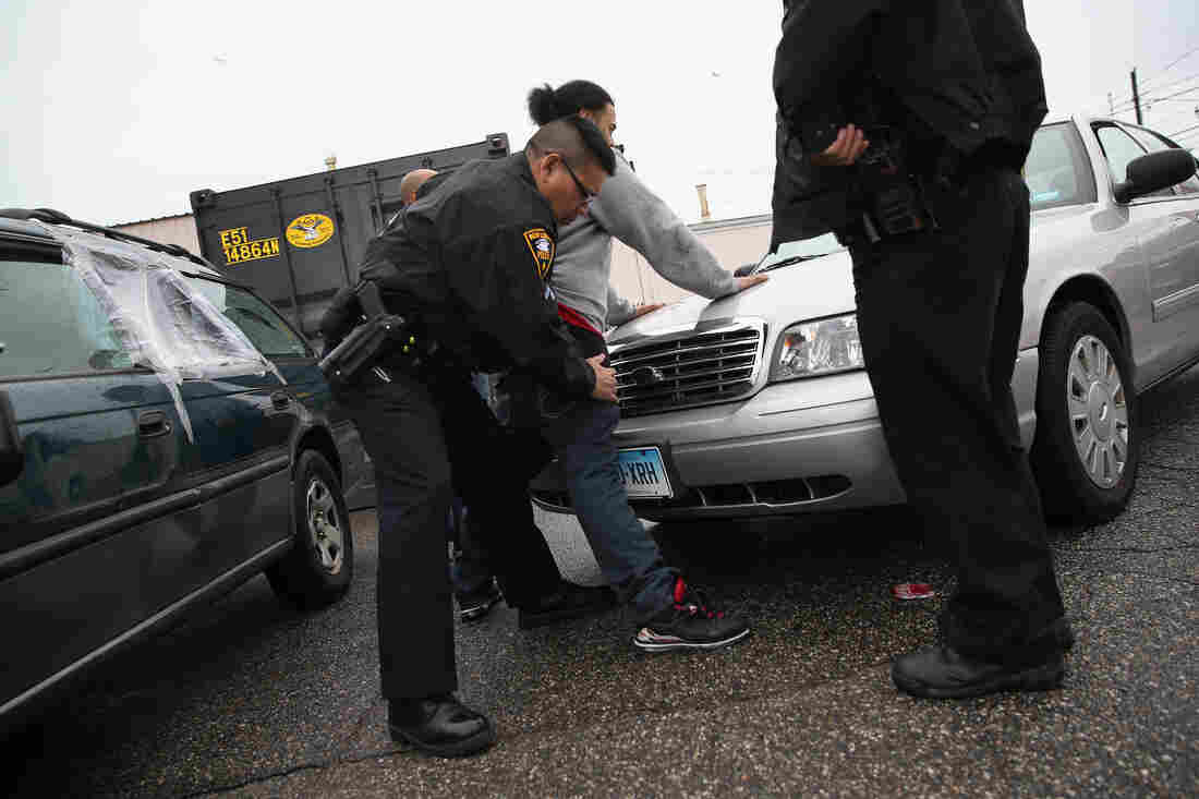 Police officers search a suspect for heroin on March 14, in New London, Conn. Police say an increasing number of suburban addicts are coming into the city to buy the drug, which is much cheaper than opioid painkillers.