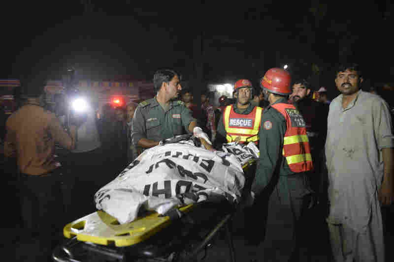 Rescuers use a stretcher to shift a body from Gulshan-e-Iqbal park on Sunday.