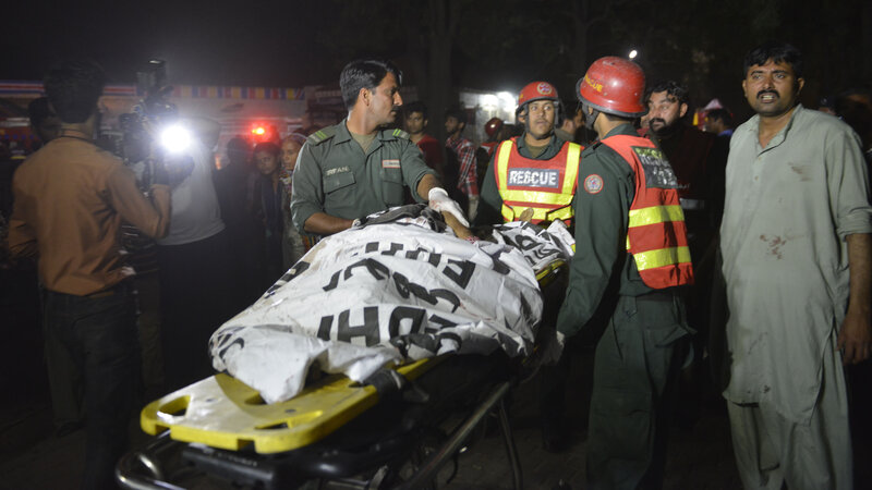 Rescuers use a stretcher to shift a body from a bomb blast site in Lahore, Pakistan, on Sunday.