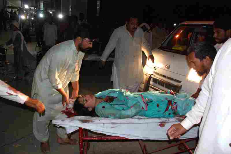 Relatives bring an injured woman to a hospital in Lahore.