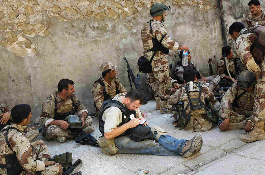 Michael Ware takes notes while reporting with the U.S. military in Iraq.