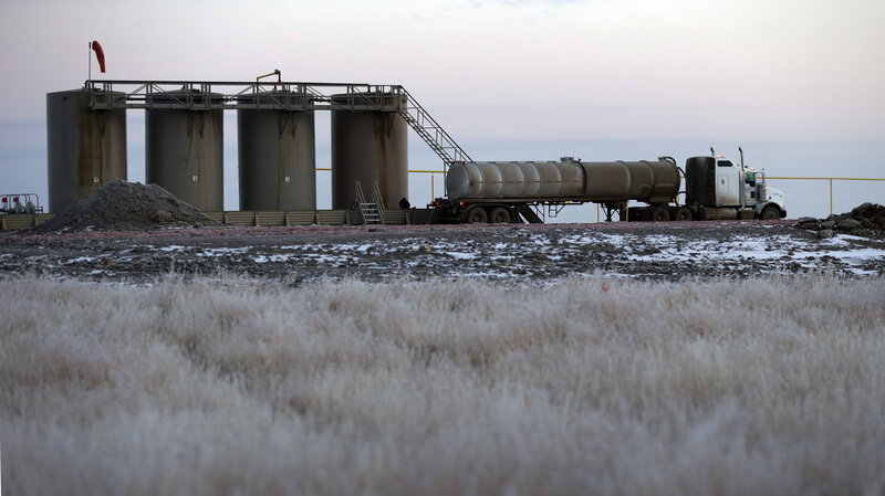 An oil field truck is used to make a transfer at oil-storage tanks in Williston, N.D., in 2014. It was atop tanks like these that oil worker Dustin Bergsing, 21, was found dead.