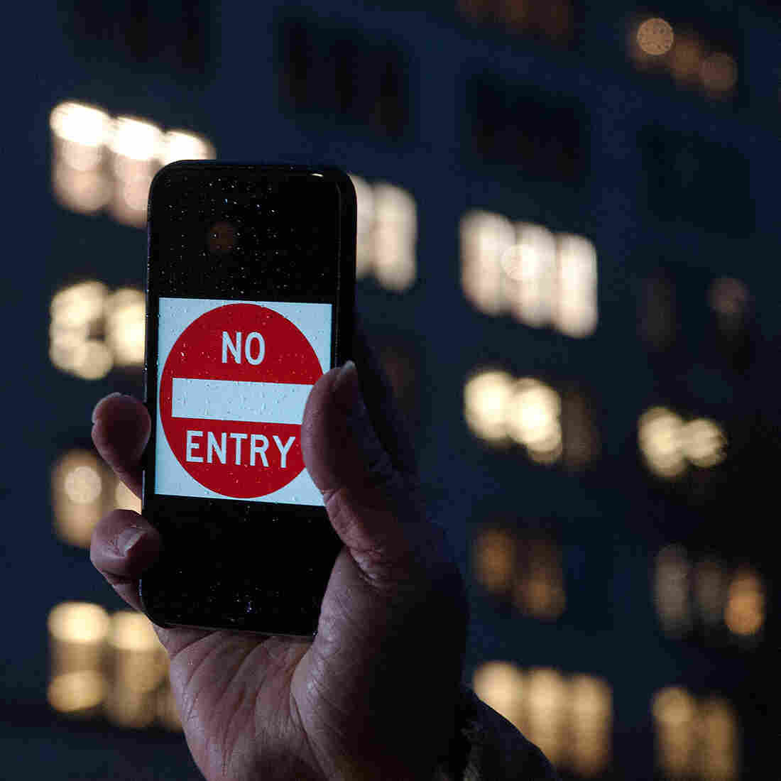 "A protester supporting Apple in its battle against the FBI holds up an iPhone that reads ""No Entry"" outside an Apple store in New York on Feb. 23."