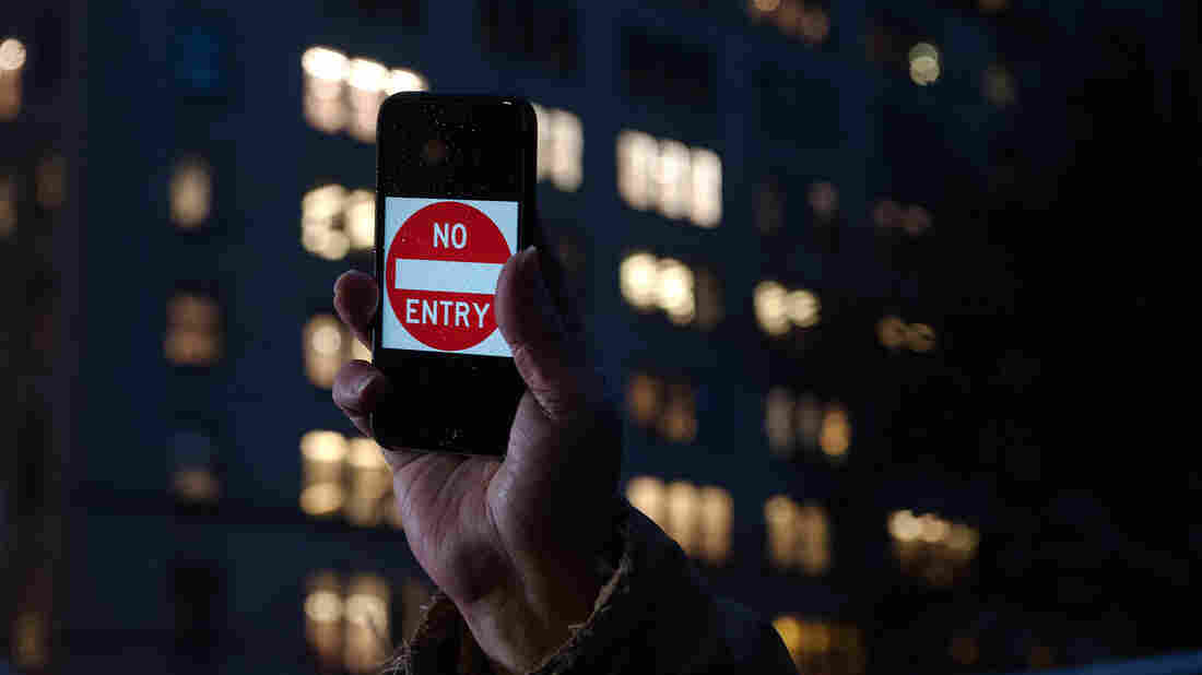 "A protester supporting Apple in its battle against the FBI holds up an iPhone that reads, ""No Entry"" outside an Apple store in New York on Feb. 23."