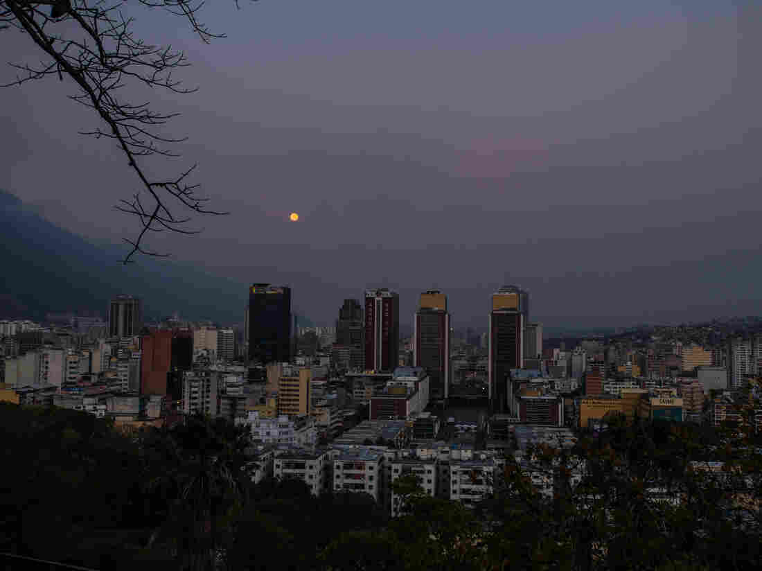 The headquarters of the Bank of Venezuela (from left) and buildings housing the National Assembly and various government ministries stand in darkness in Caracas on March 22. Venezuela shut down for a week to conserve electricity amid a deepening power crisis.