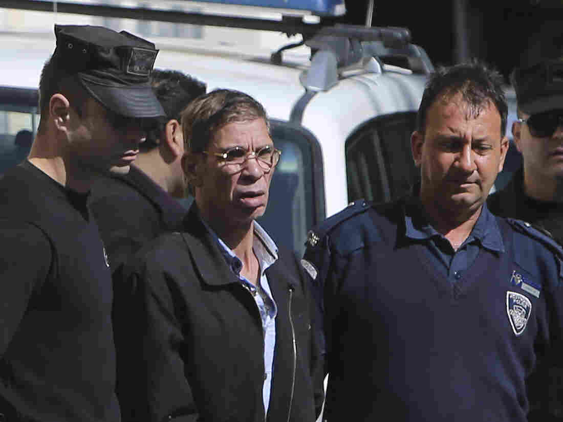 EgyptAir hijack suspect Seif Eldin Mustafa (middle) is escorted by Cypriot police officers as he leaves a court after a remand hearing in Cyprus.