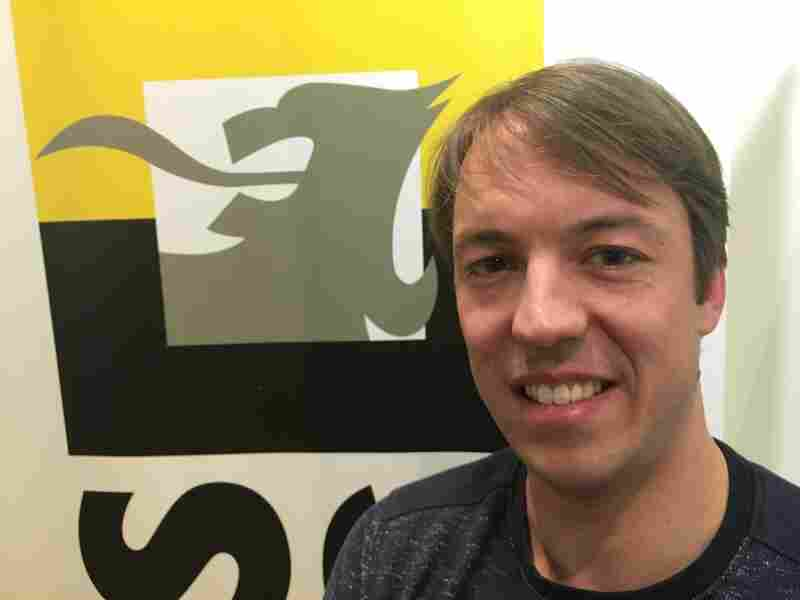 Sam van Rooy stands next to the Flemish lion logo of Vlaams Belang, or Flemish Interest Party, the far-right Belgian political party for which he is the spokesman.