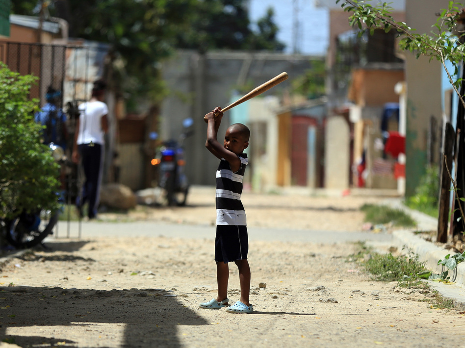 A boy is ready to take a swing on the streets of San Pedro de Macoris, a provincial capital of the Dominican Republic. (Terrence Antonio James/Chicago Tribune/TNS via Getty Images)